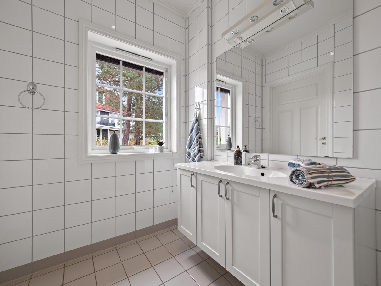 Bad i 1. etg. er innredet med vegghengt toalett, dusjhjørne og servantinnredning.