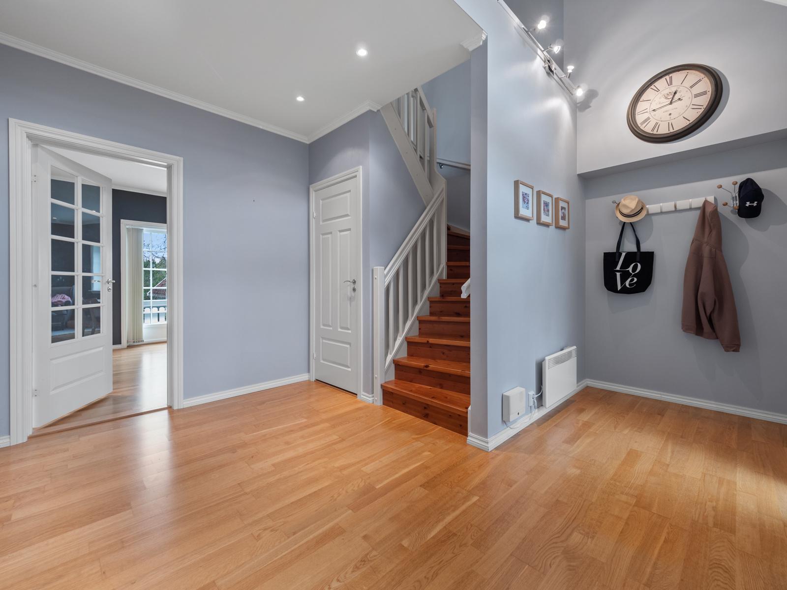 Entre/hall med praktisk garderobehjørne og bod under trapp.