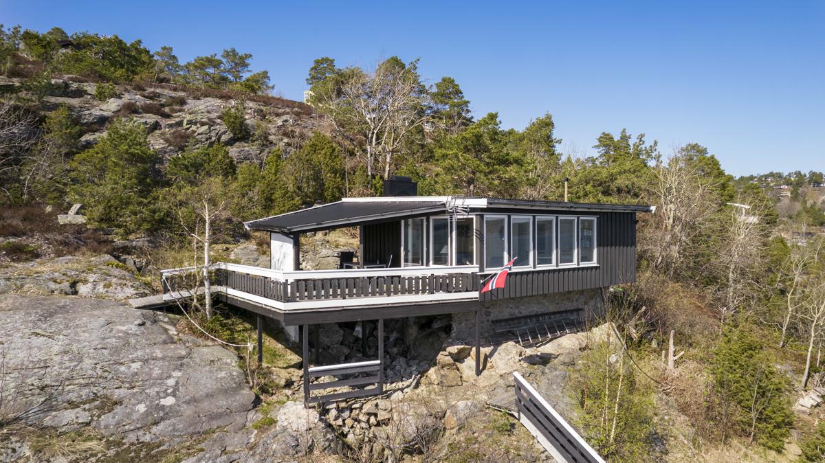 Hytta har stor terrasse mot sjøen, ellers er tomten i hovedsak naturtomt