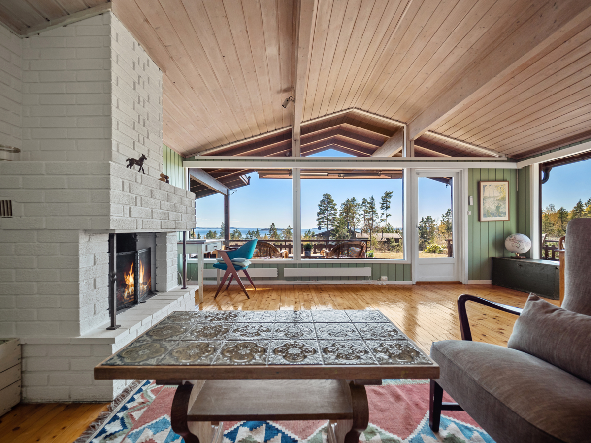 Stue med peis og store vindusflater som gir gode lys- og utsiktsforhold