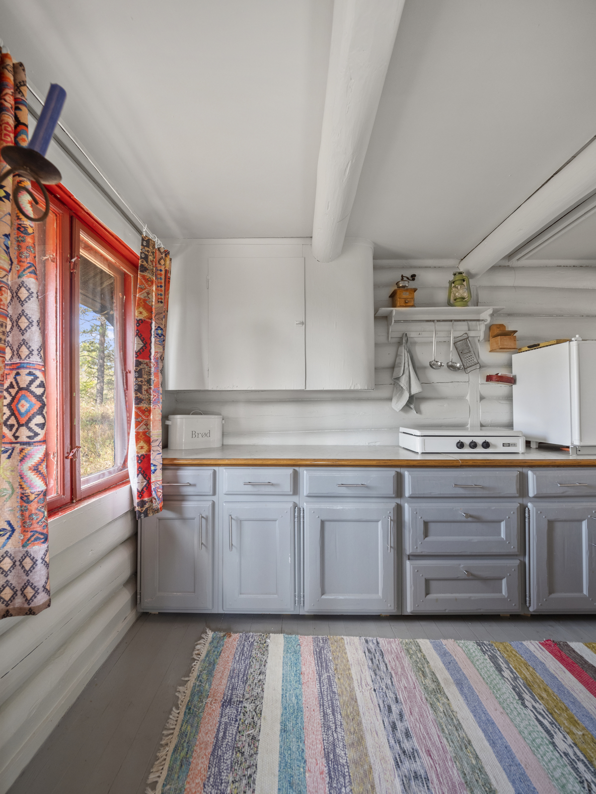 Kjøkken med malt innredning, med godt med benk- og oppbevaringsplass