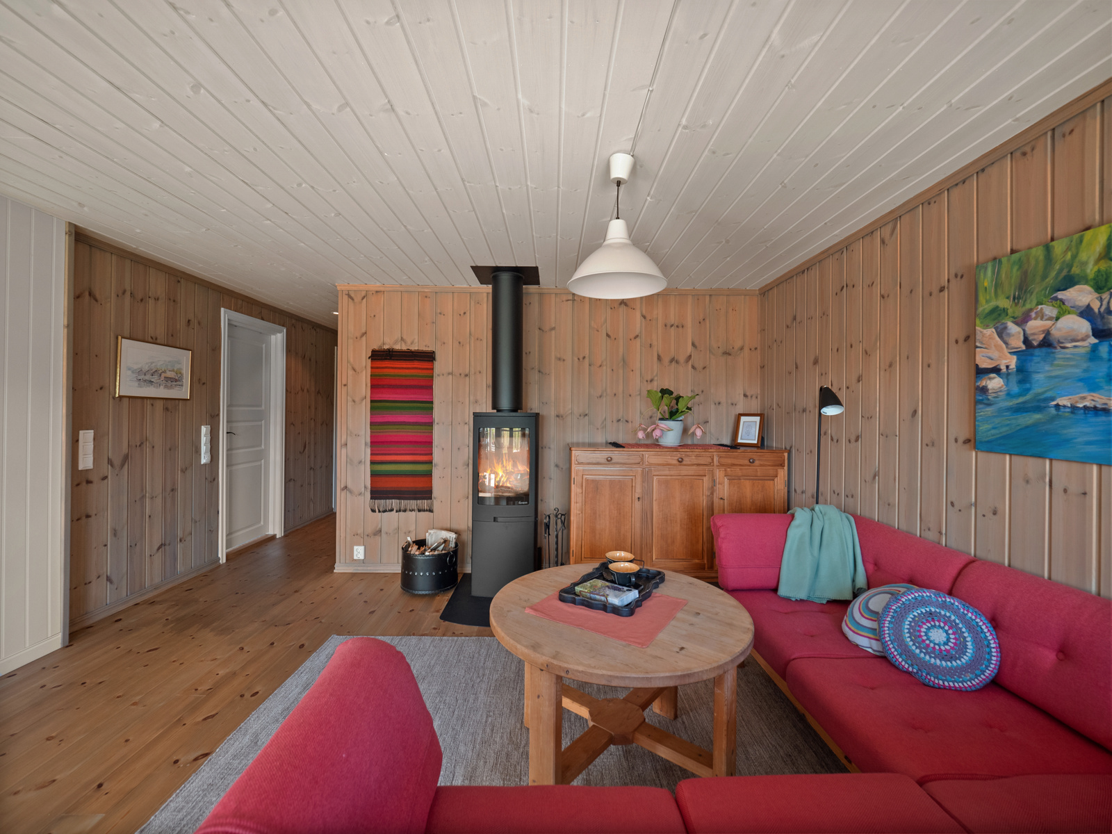 Hyggelig stue med tregulv, panel på vegger og i himling