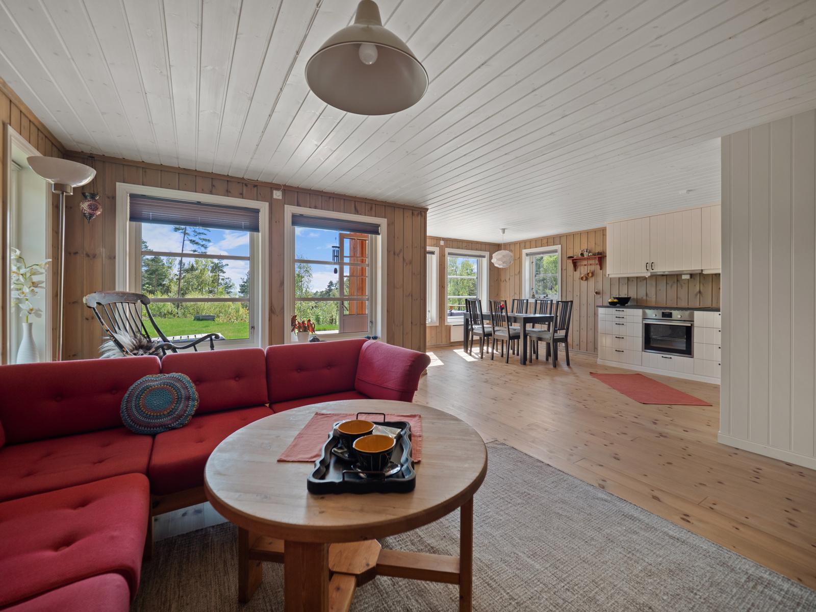 Stue og kjøkken i åpen løsning sammen med store vinduer som gir rommet en lys og hyggelig atmosfære
