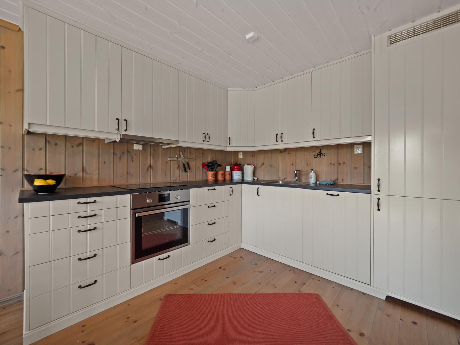 Kjøkkeninnredning med integrert platetopp, komfyr, oppvaskmaskin og kjøl/frys