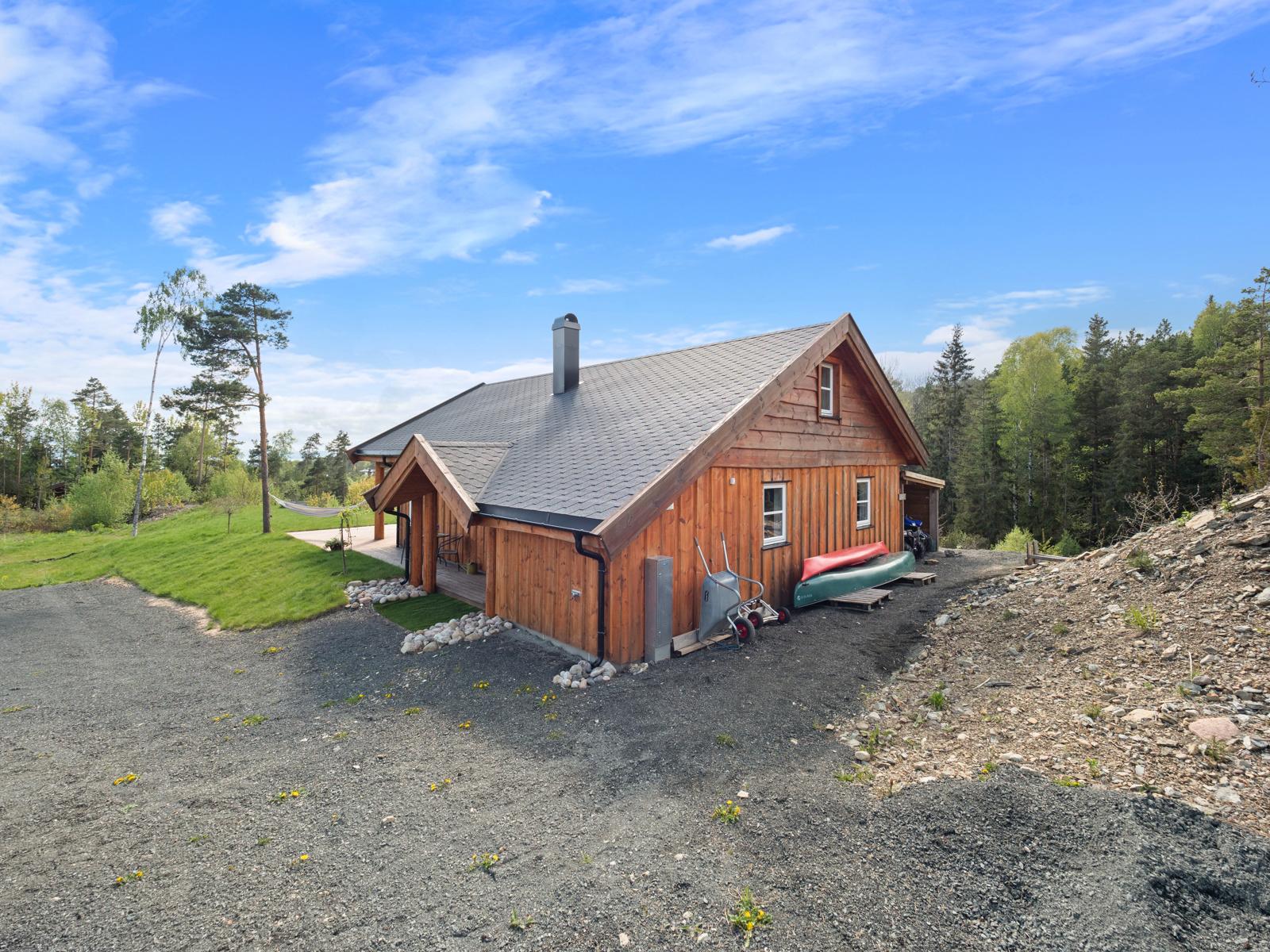 Tomten er opparbeidet med gårdsplass, terrasse, gressplen og noe naturtomt