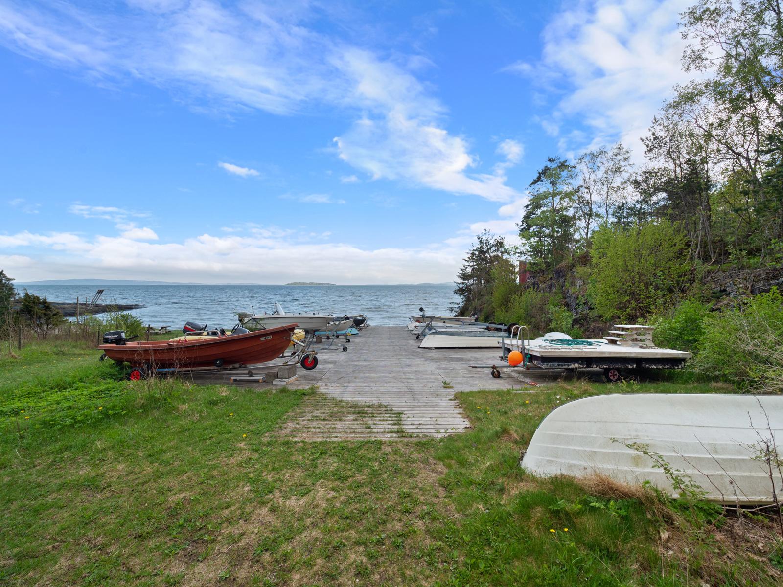 Båtopptrekket med elektrisk vinsj, badeplattform, brygge og volleyballbane som driftes av hyttevelet.