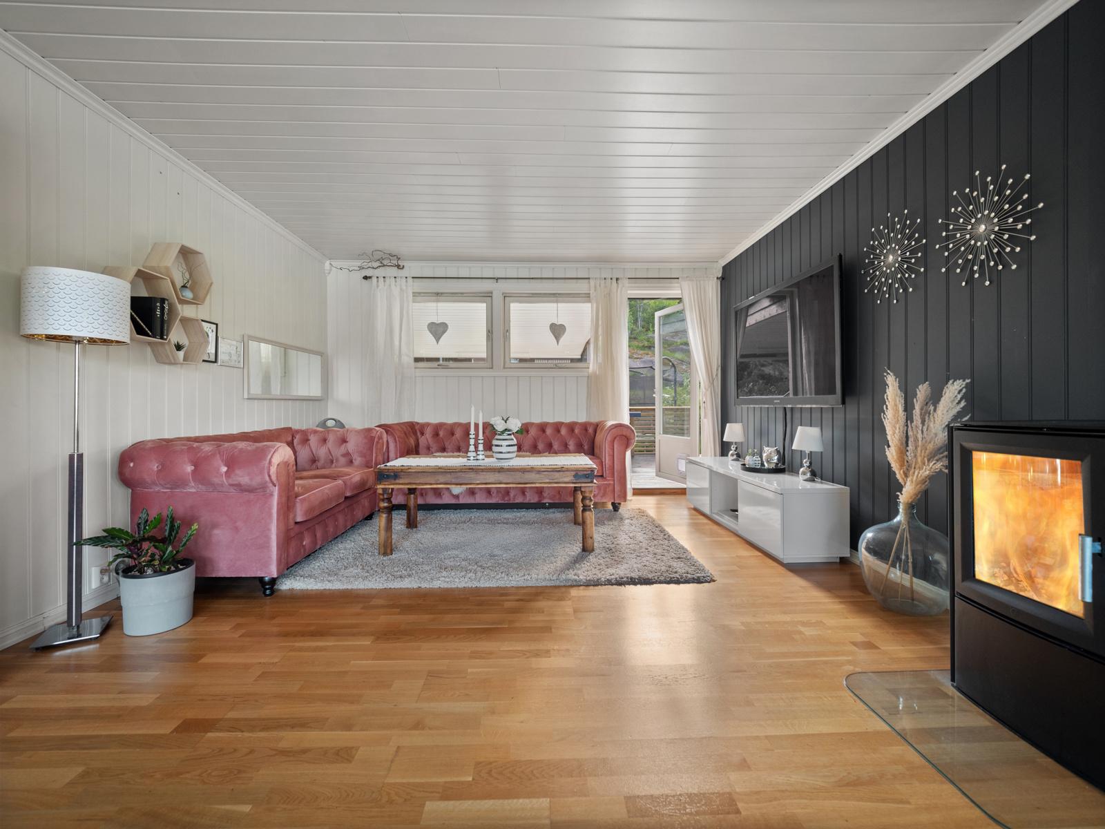 Stue med peisovn og utgang til terrasse