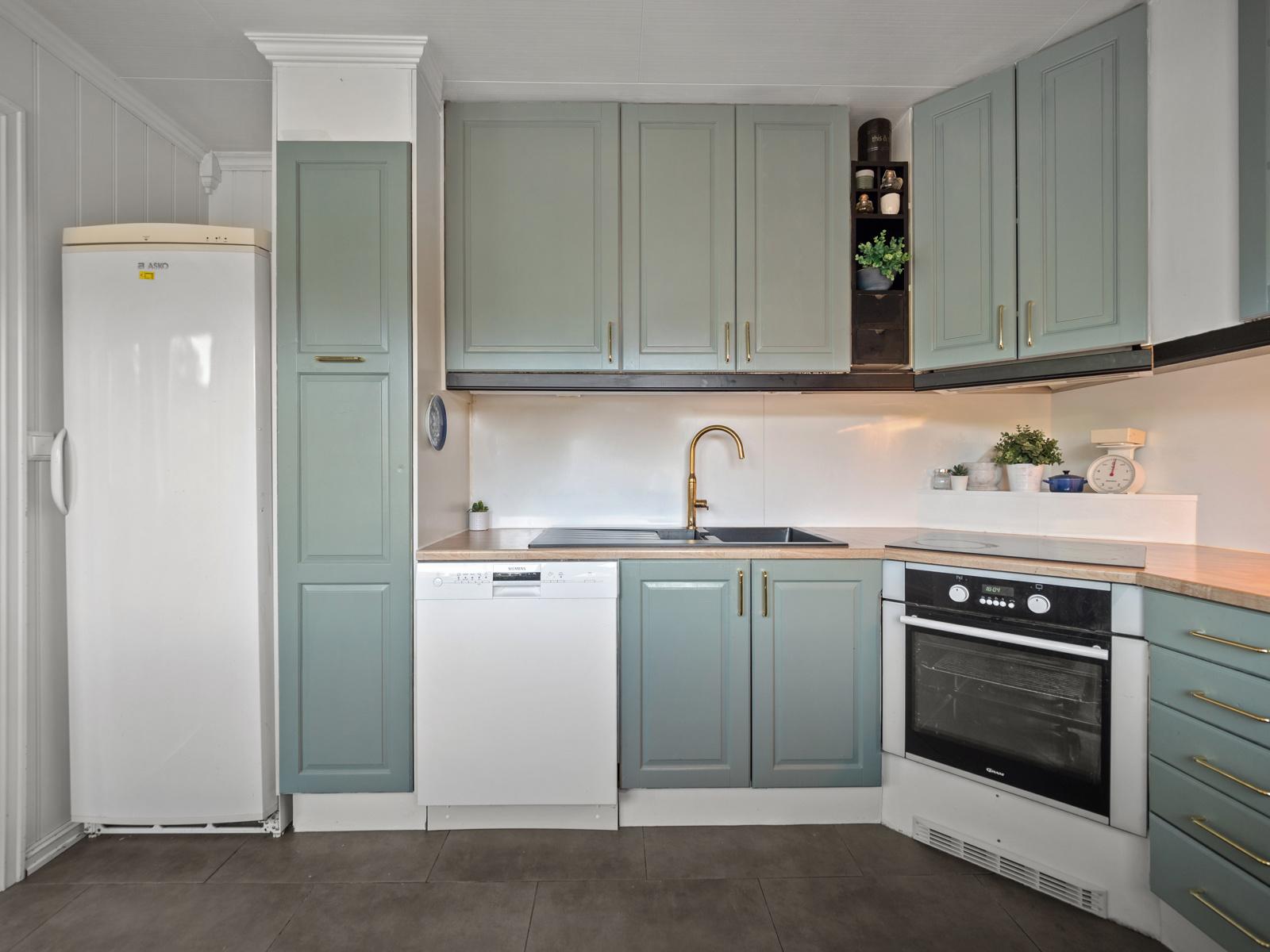 Innredning med integrert platetopp og stekeovn - Videre er det oppvaskmaskin og avsatt plass til kjøl/frys