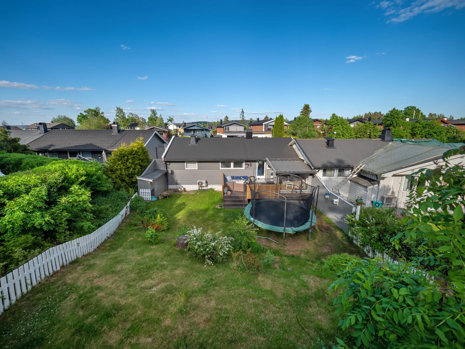 Hyggelig terrasse og hage med gressplen og diverse beplantning