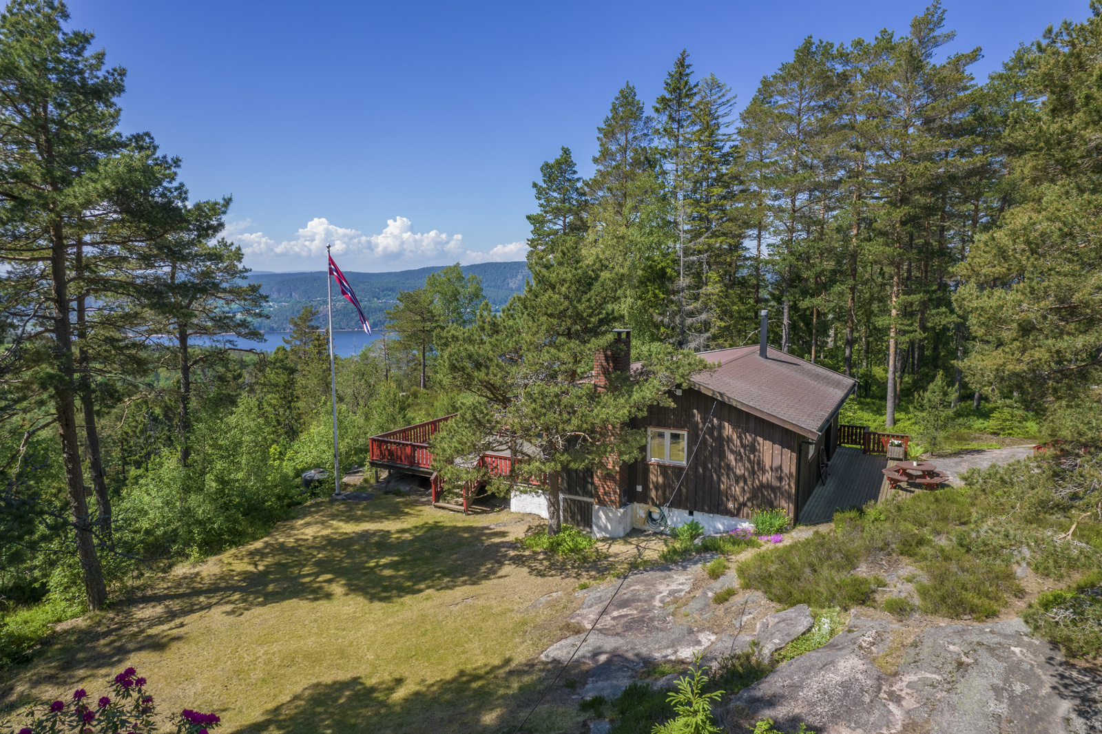 Hytta ligger flott til på eiendommen med stor terrasse - Perfekt for late dager i solen