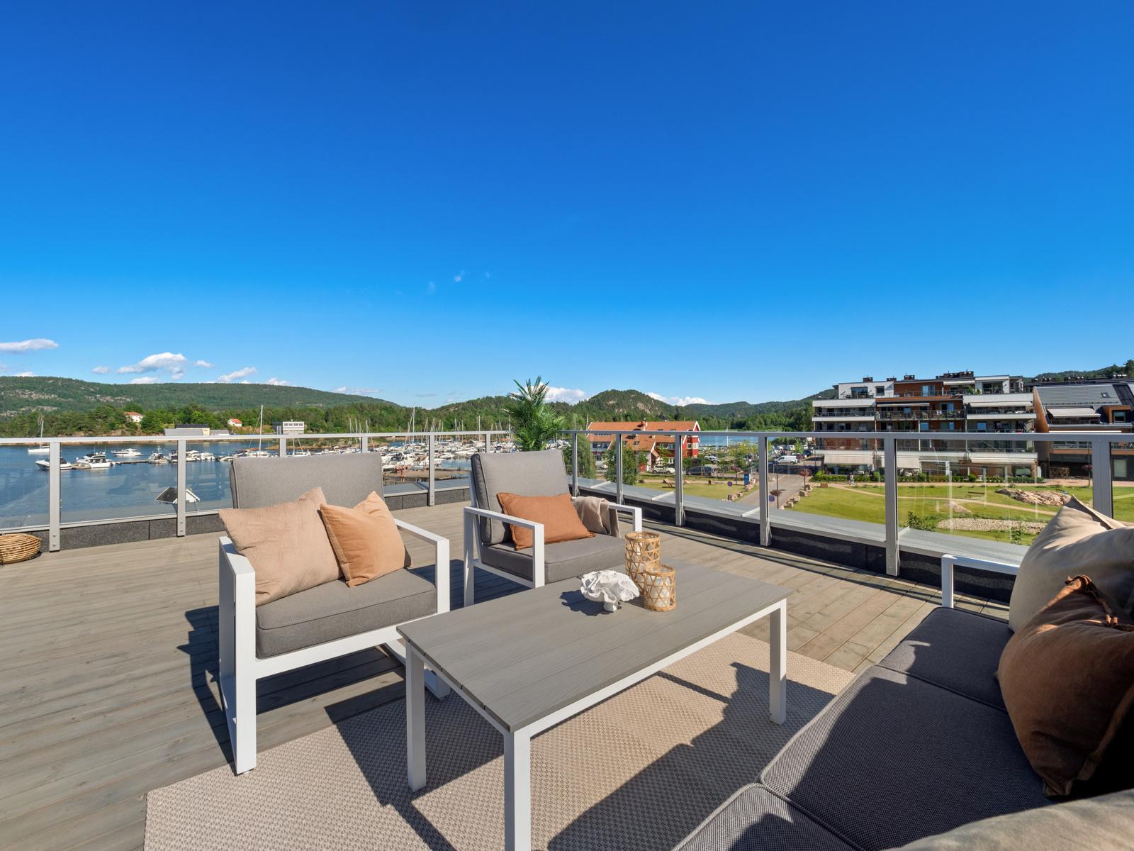 Boligen har privat takterrasse med fritt utsyn utover fjorden, stranden og Sætre sentrum