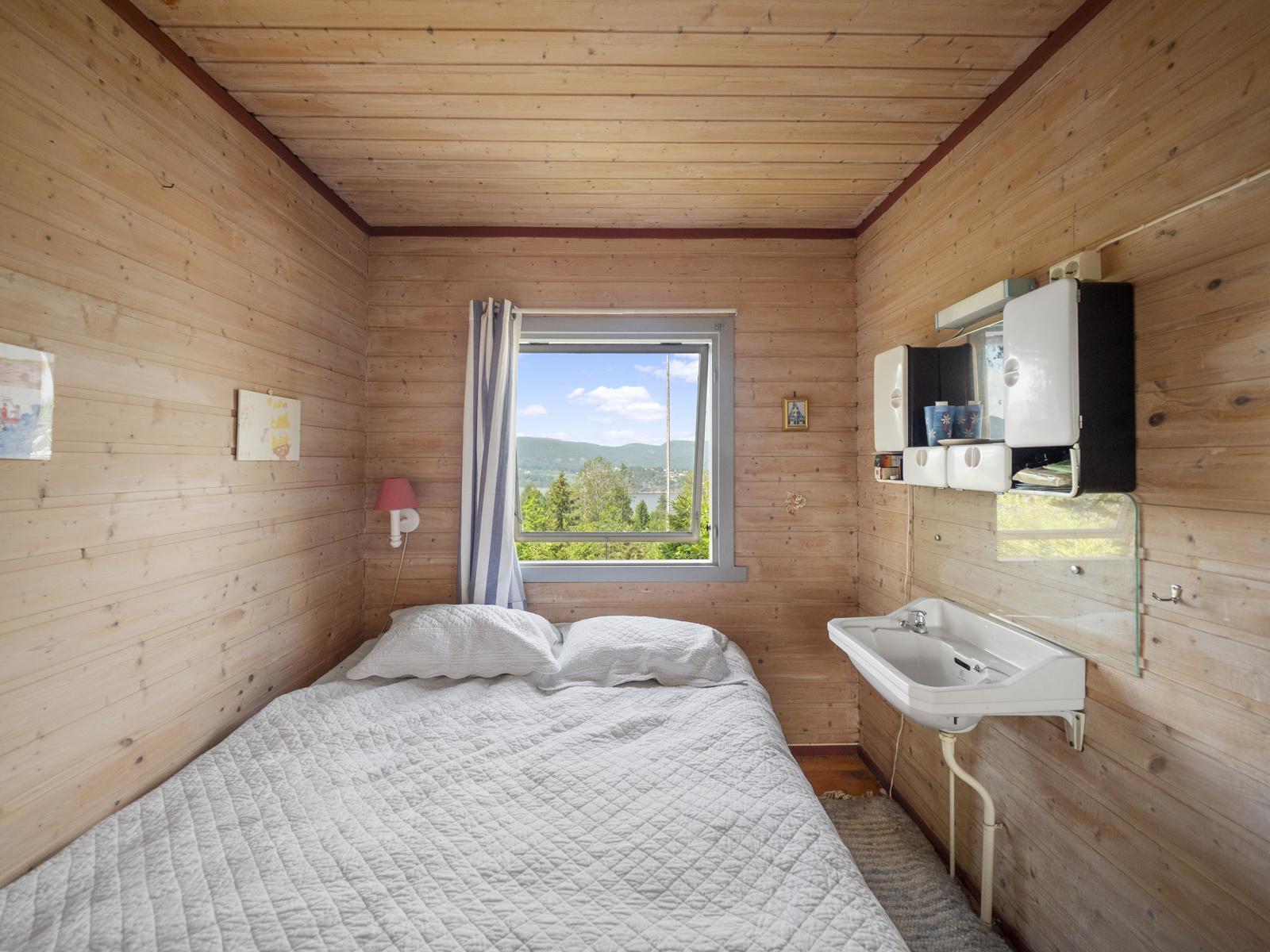 Hovedsoverommet har servant og stort vindu med hyggelig utsikt
