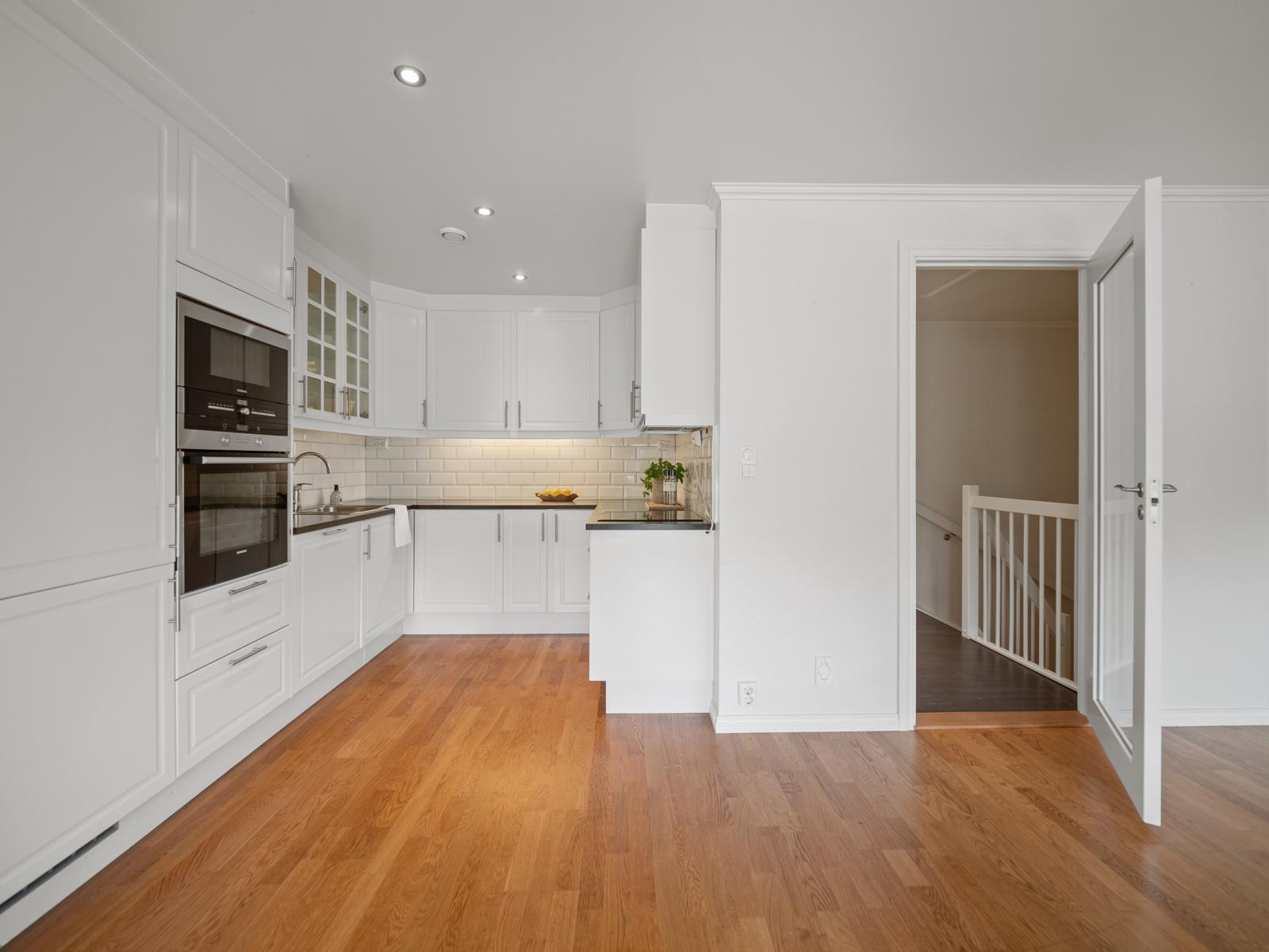 Kjøkken med innebygde hvitevarer.