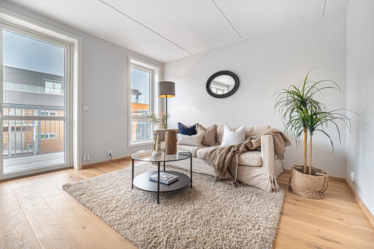 Lys og hyggelig stue med store vinduer som gir gode lys- og utsiktsforhold
