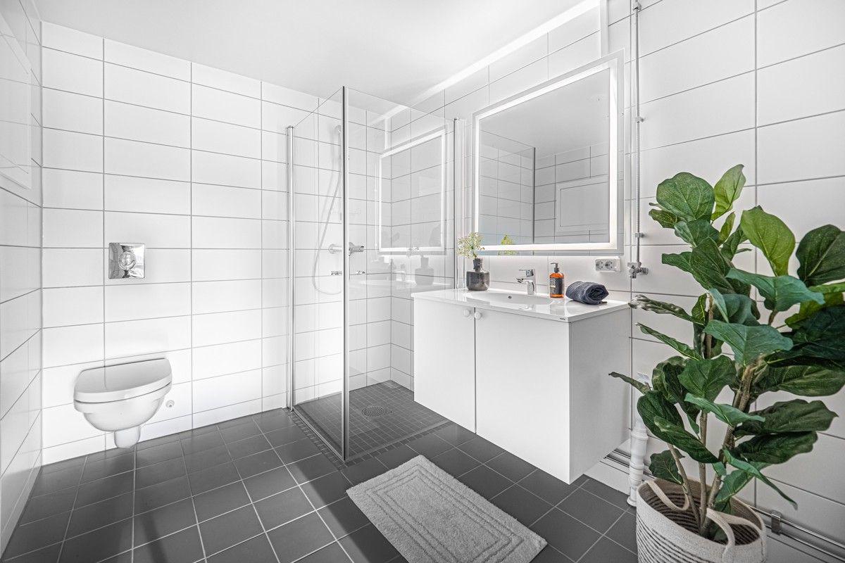 Bad med dusj, vegghengt wc, servantinnredning og opplegg for vaskemaskin