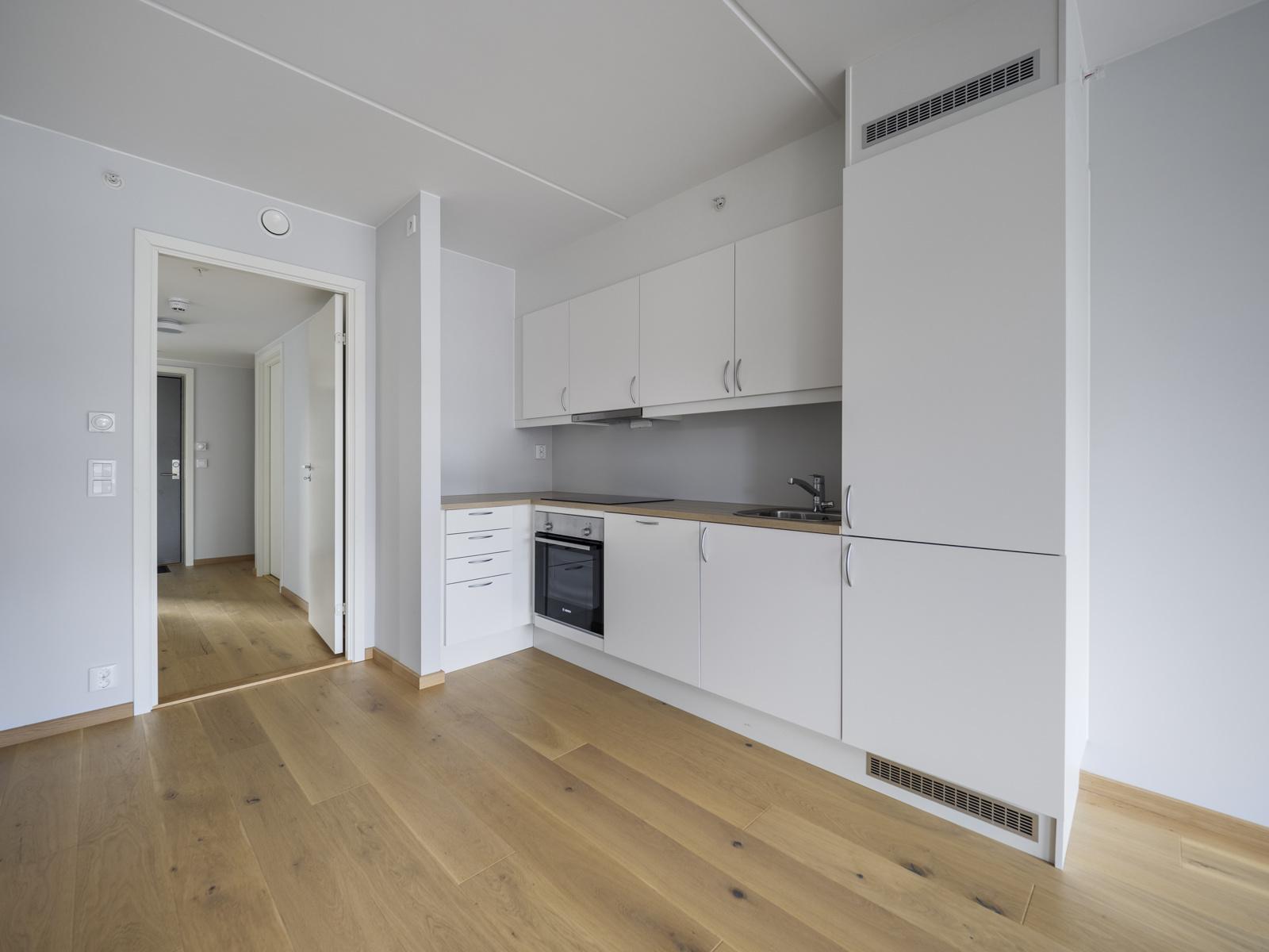 Kjøkken med hvite fronter og integrerte hvitevarer som platetopp, stekeovn, kjøl/frys og oppvaskmaskin