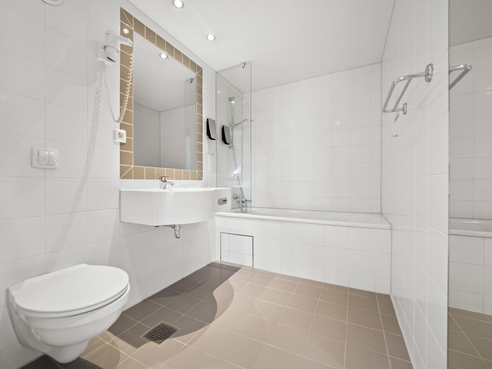 Bad I med vegghengt wc, badekar med dusjløsning og servant
