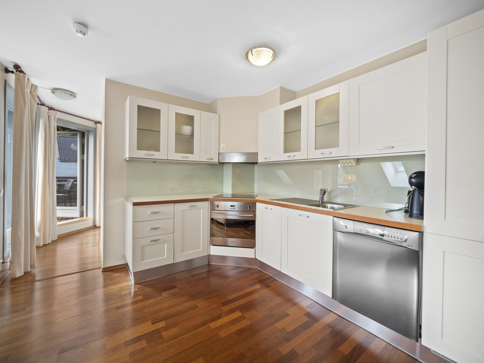 Kjøkken i åpen løsning mot stue - Integrerte hvitevarer som stekeovn, platetopp pg kjøl/frys
