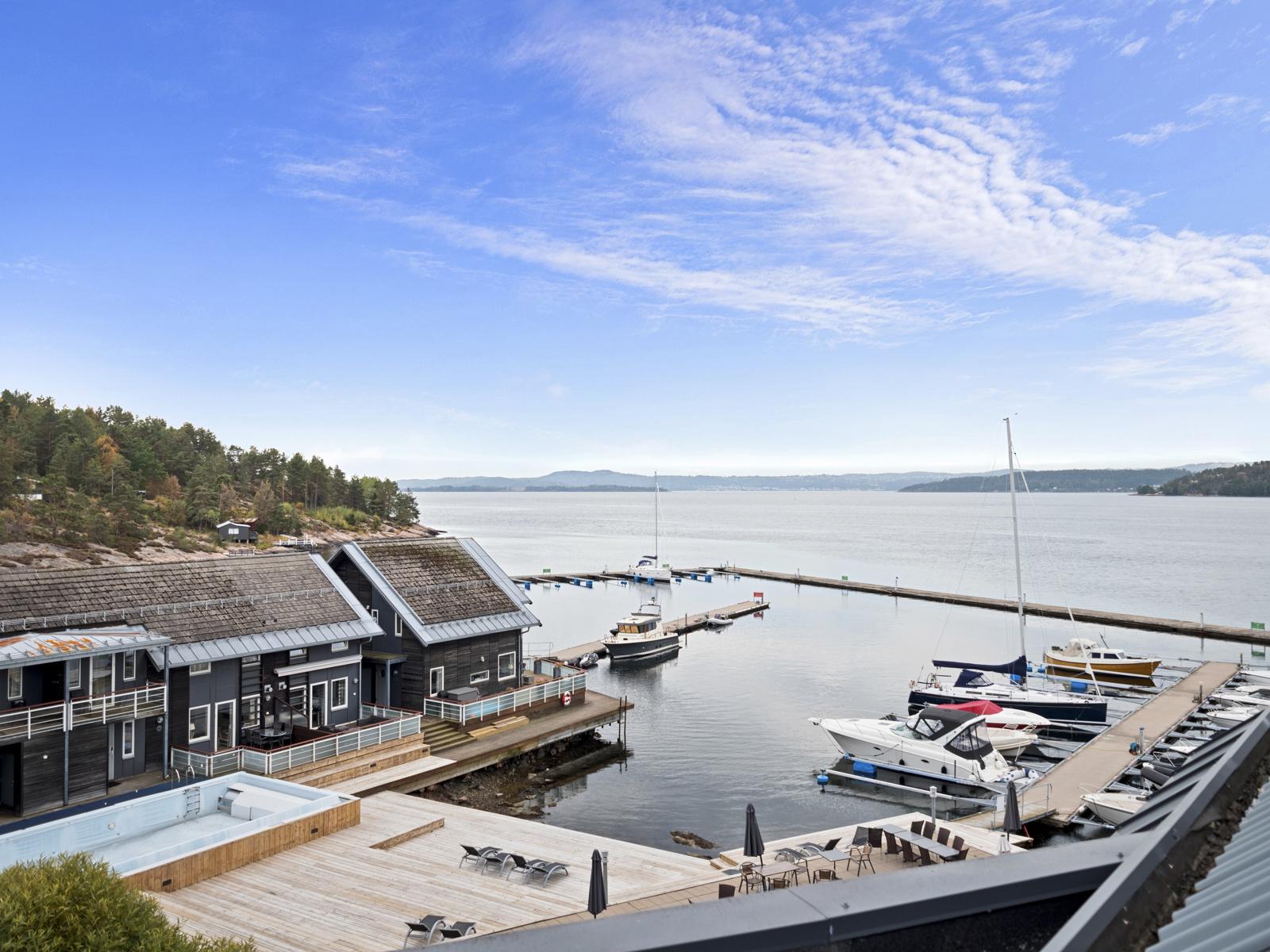 Fra terrassen er det hyggelig utsikt over fellesarealet, brygga og fjorden