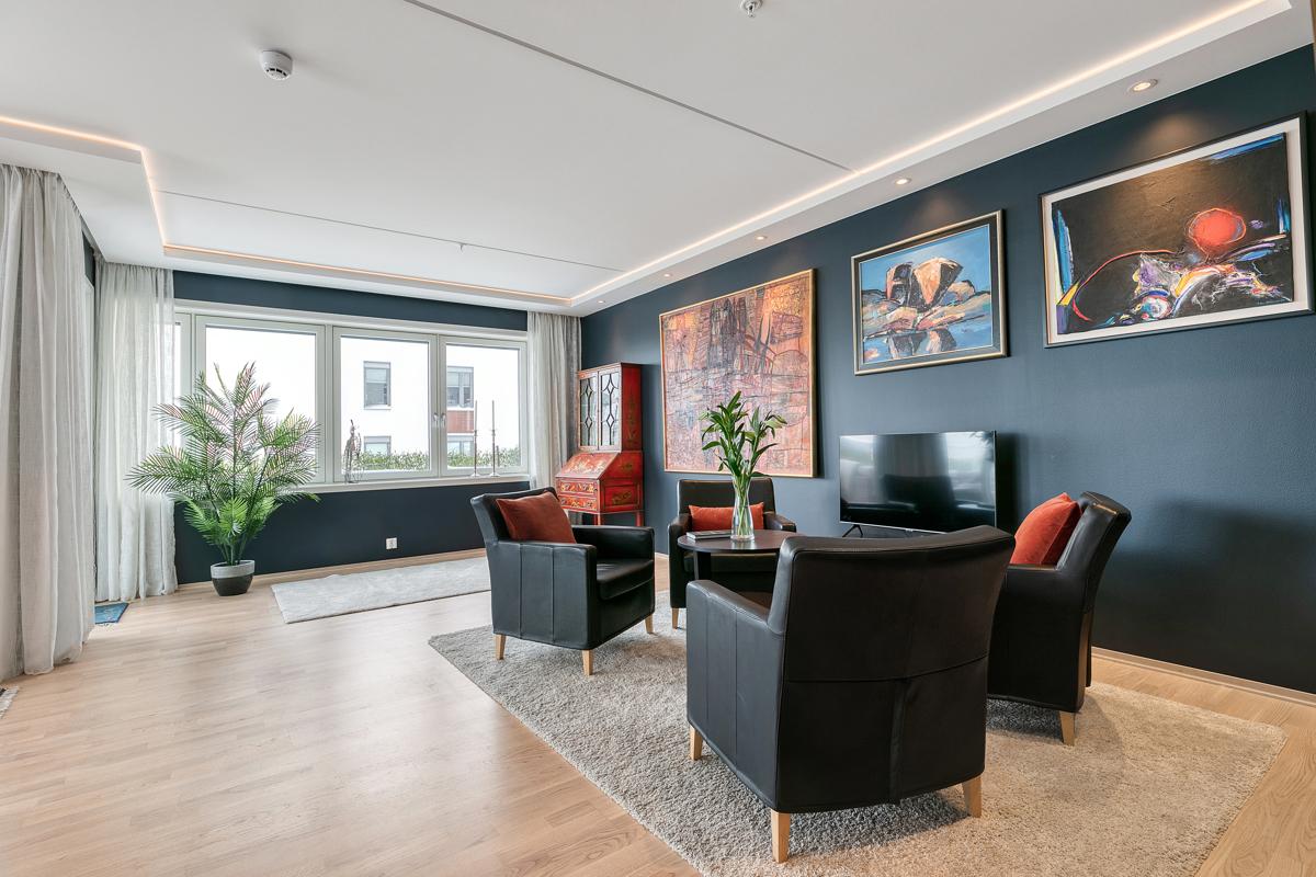 Stuen er malt i en mørk tidsriktig farge, det er godt med med lys fra de store vindusflatene