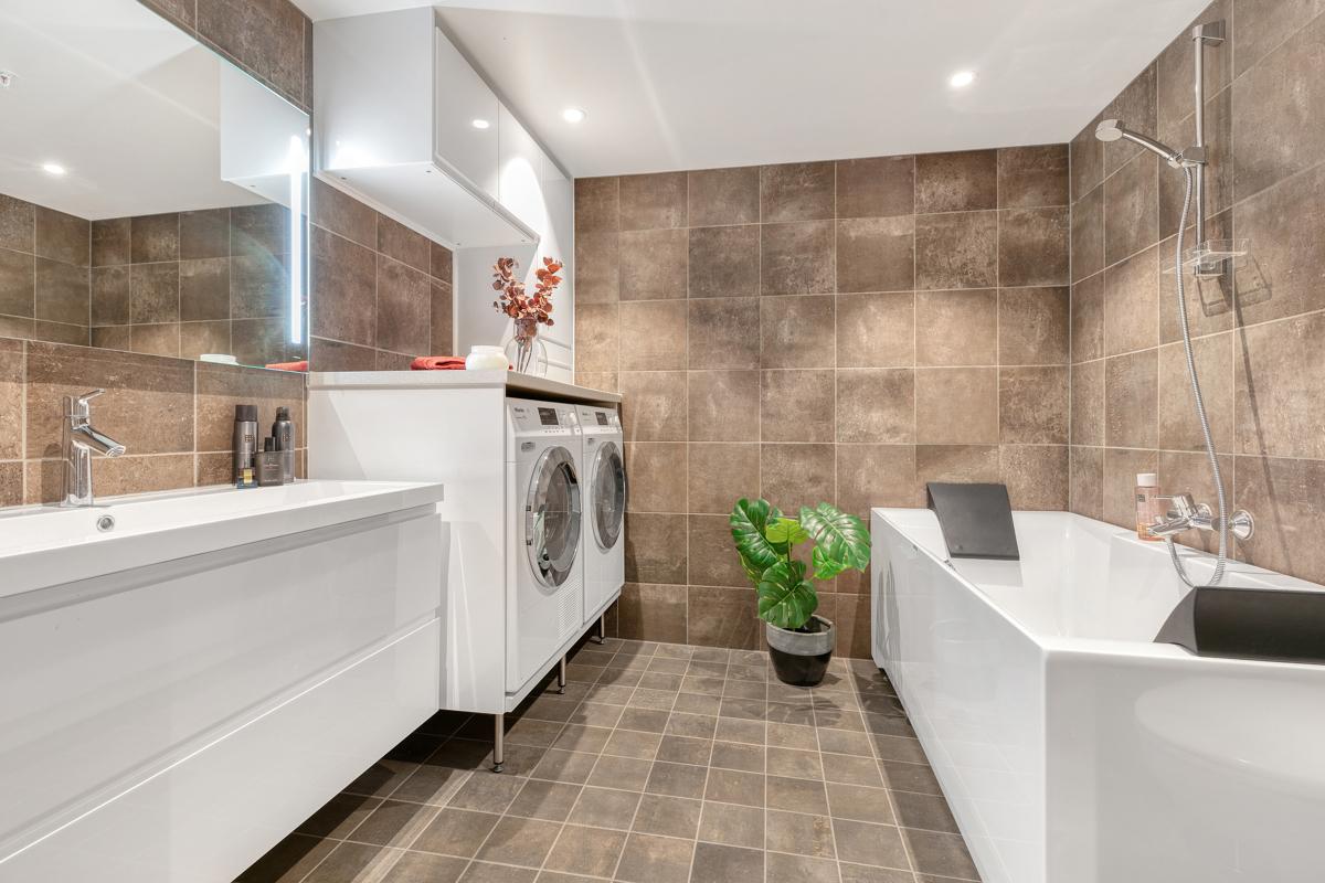 Pent flislagt bad med badekar og opplegg for vaskemaskin