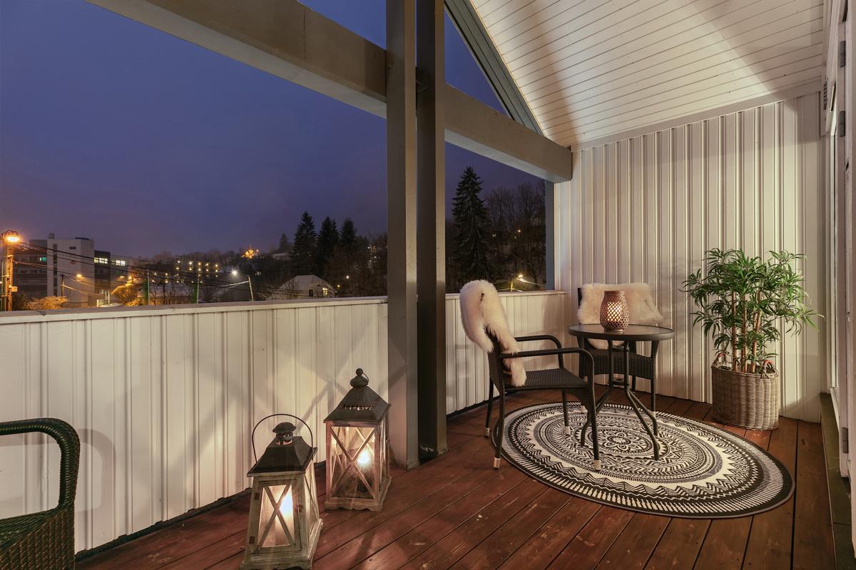 Romselig, overbygd, lun og koselig veranda med utsikt over nærområdet.