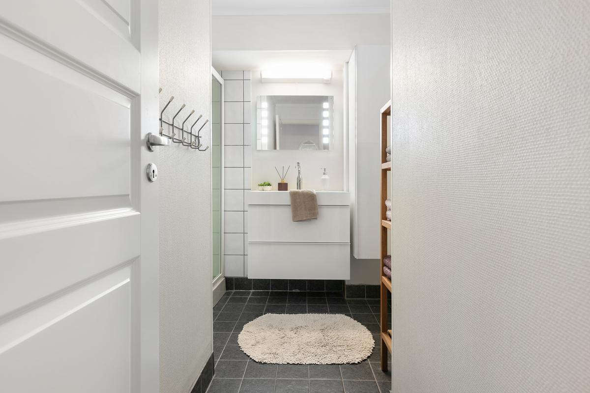 Bad i 1. etasje. Det er fliser på gulv og på vegger i dusj- og vaskesone.