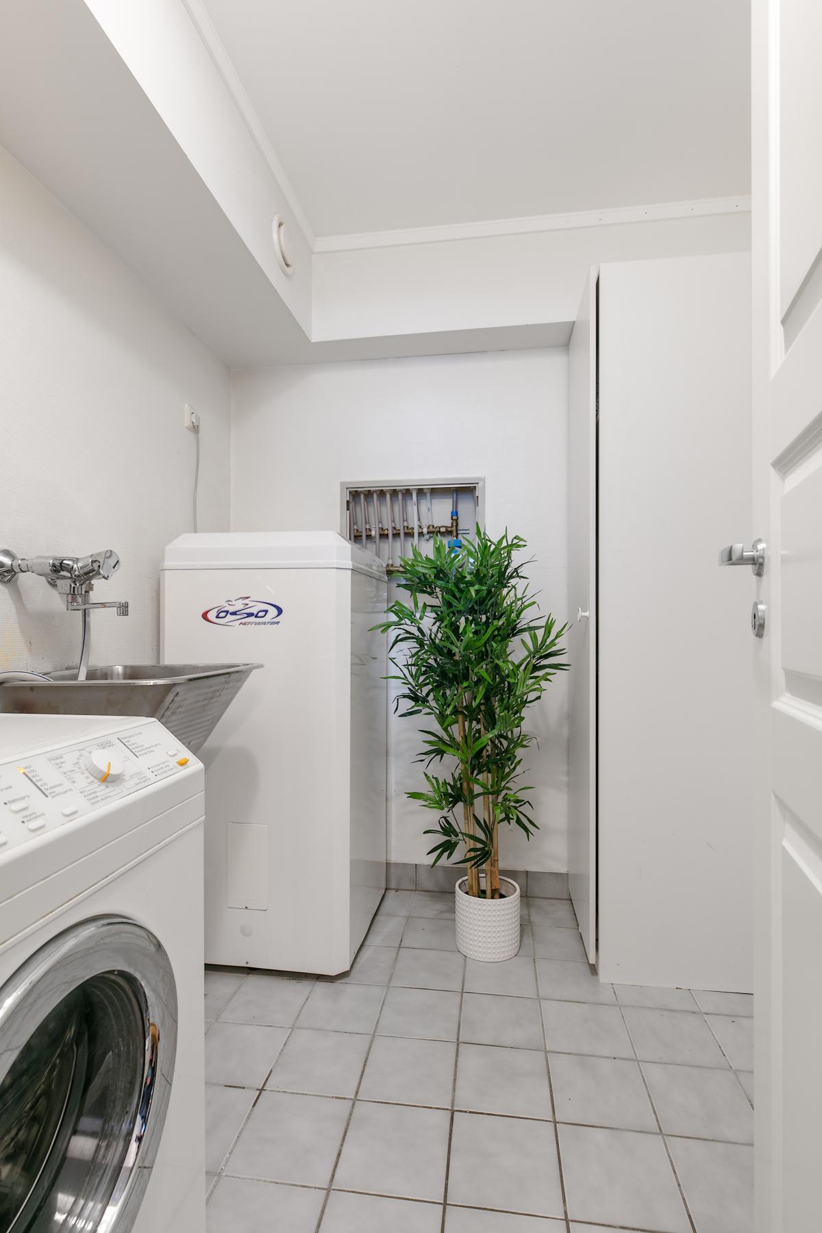 Vaskerom med gode lagrinsmuligheter. Vaskerommet ligger innenfor kjøkkenet.