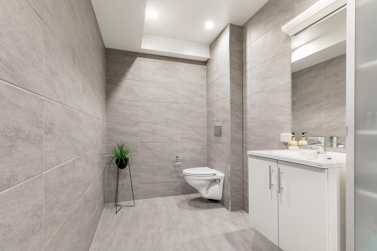 Badet har dusj, vegghengt toalett og servant med skap