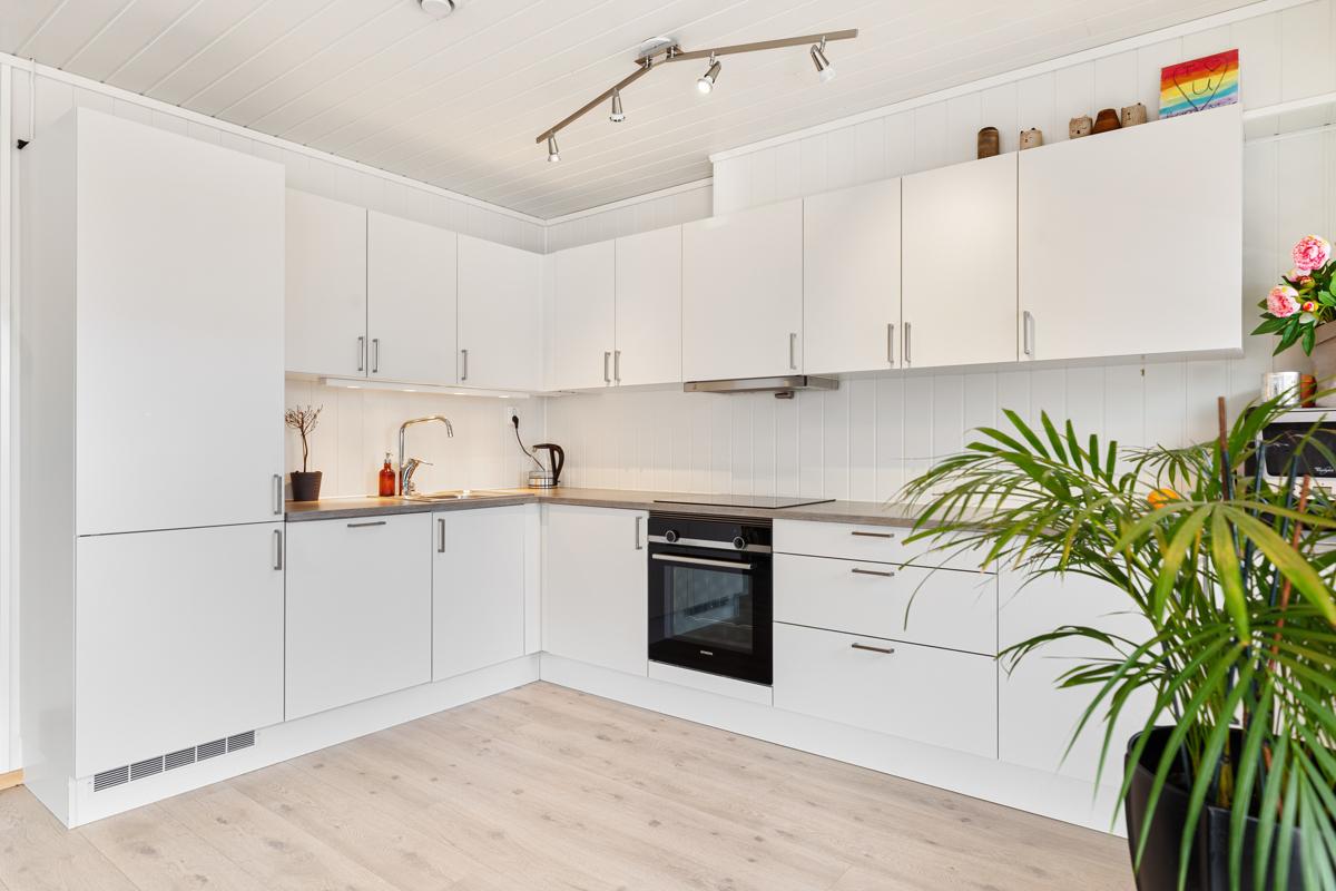Kjøkken i glatt hvit utførelse med innebygde hvitevarer, tidløst og elegant.