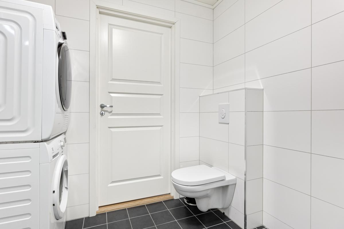 Vegghengt wc og opplegg for vaskemaskin på badet.