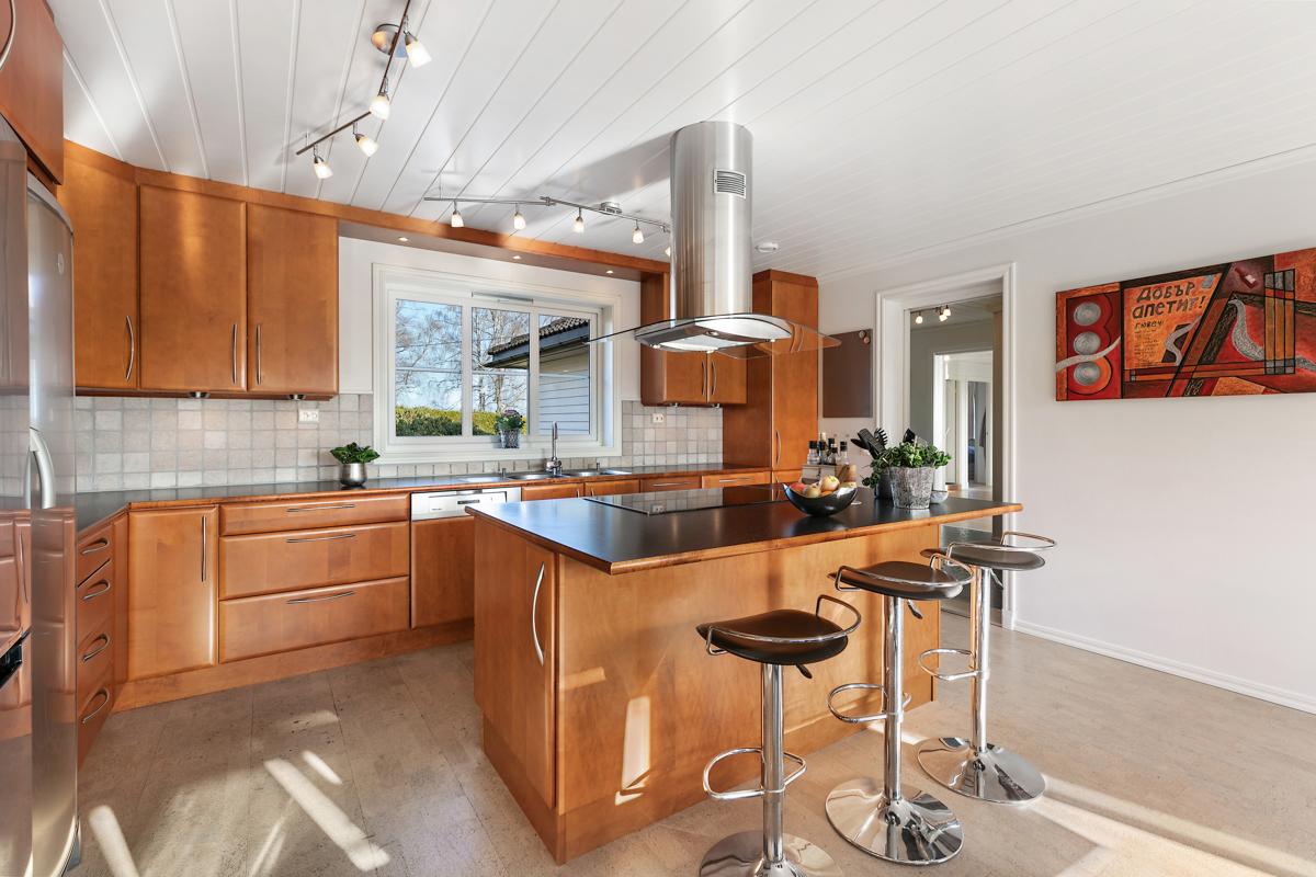 Lyst og trivelig kjøkken med glatte fronter, kokeøy med avtrekk