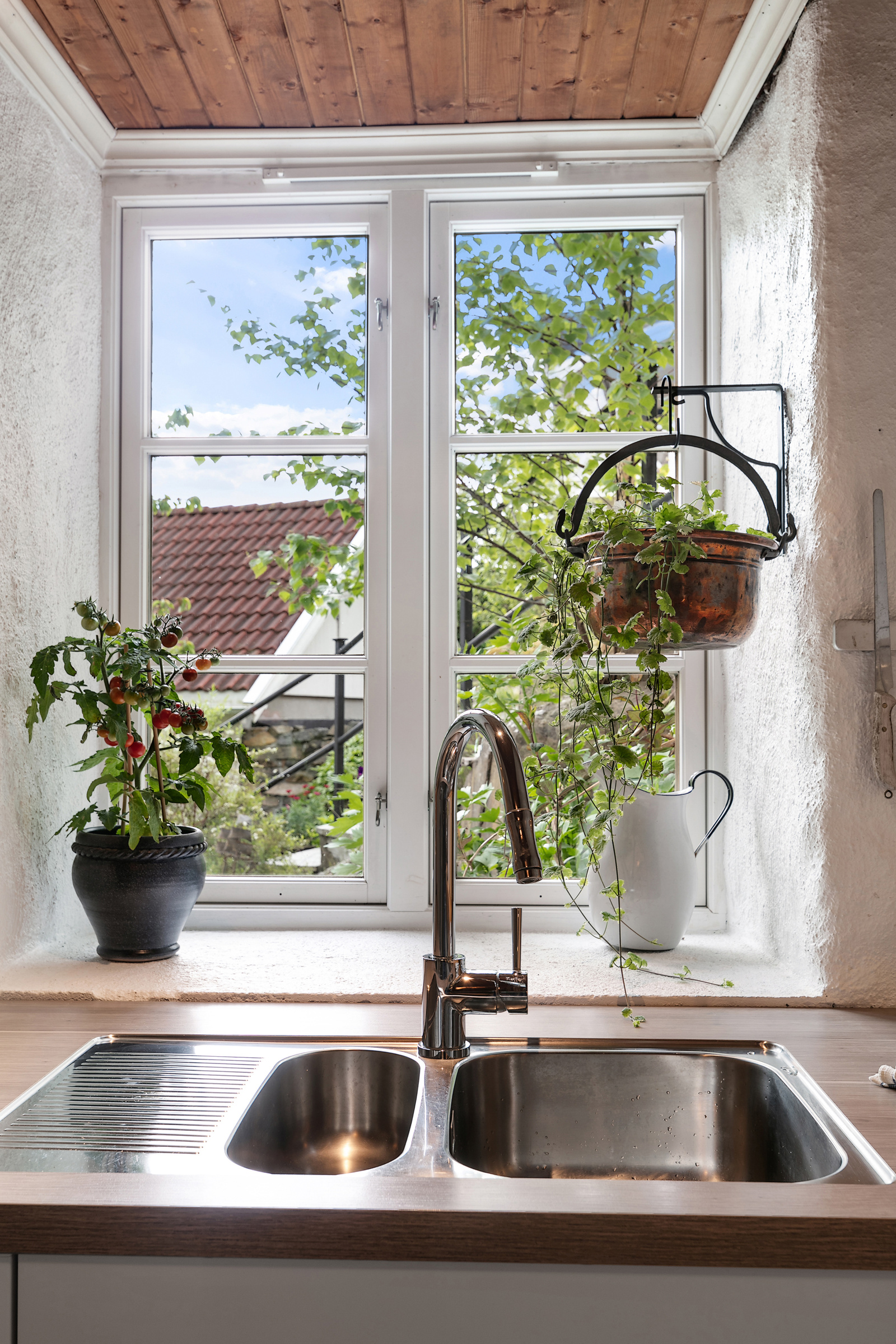 Fra kjøkkenet har du blant annet utsikt til den frodige hagen