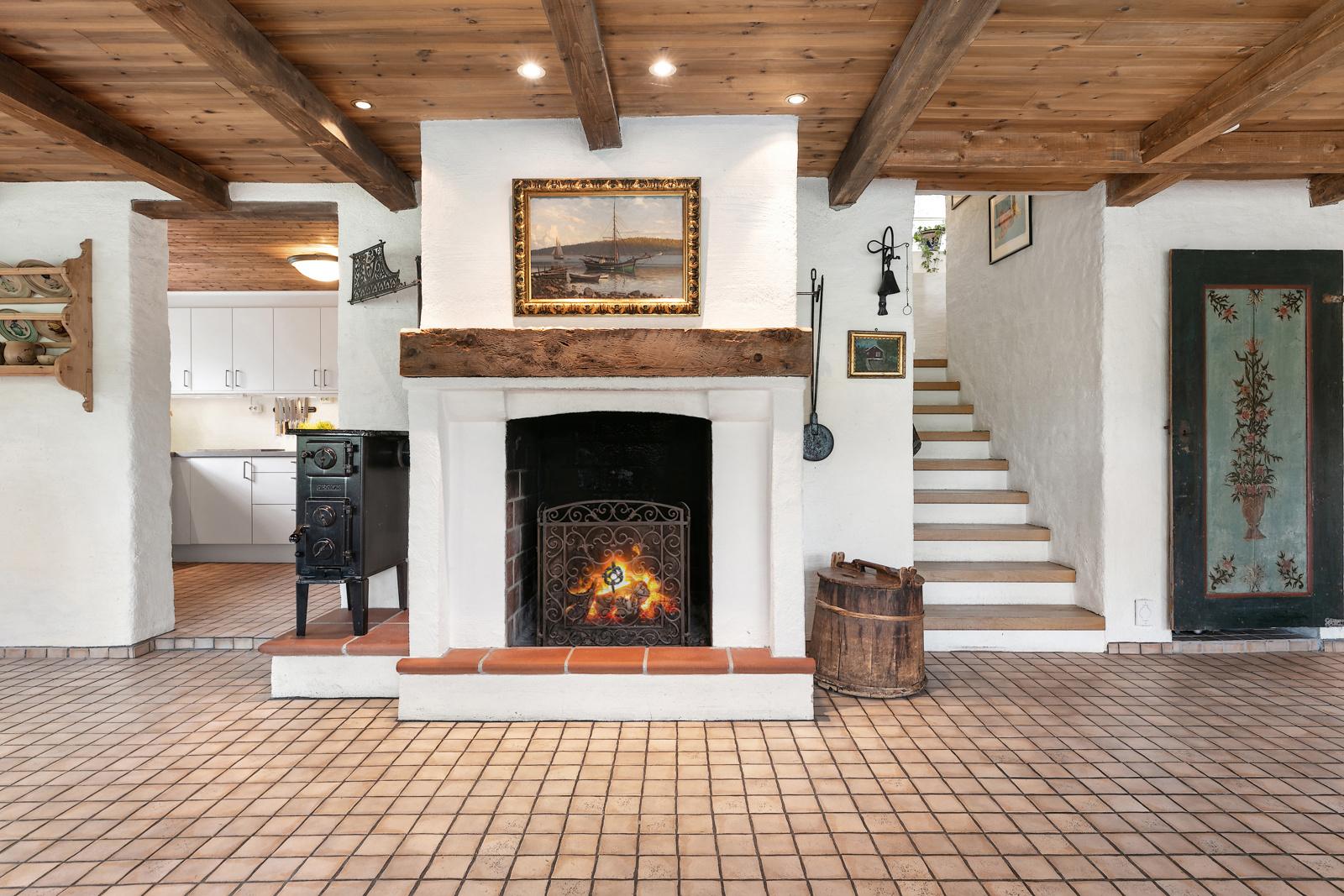 Åpen peis, inngang til kjøkken og trapp opp til stue og 1 etasje