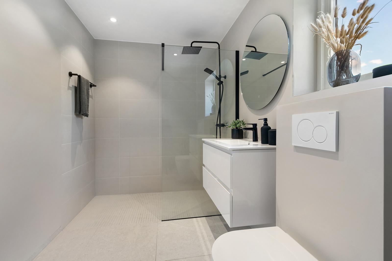 Badet har store lyse fliser og svarte detaljer