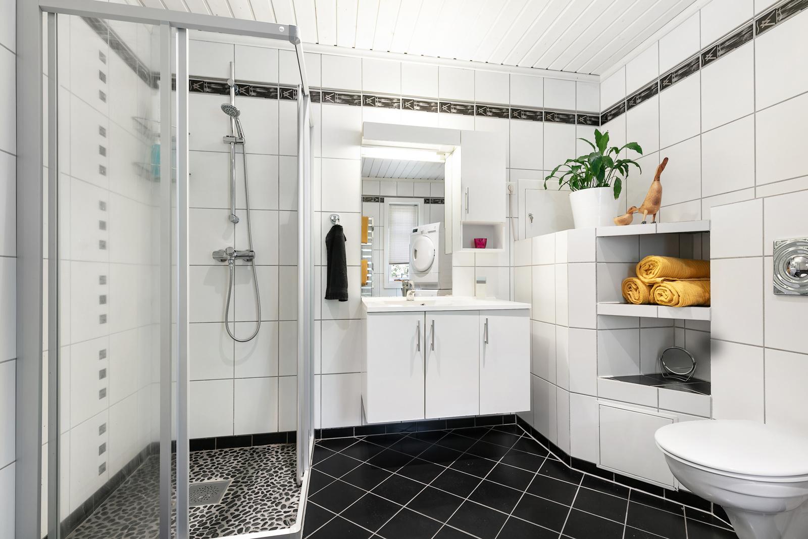 Baderommet er innredet med dusj, vegghengt toalett og servantinnredning- opplegg for vaskemaskin