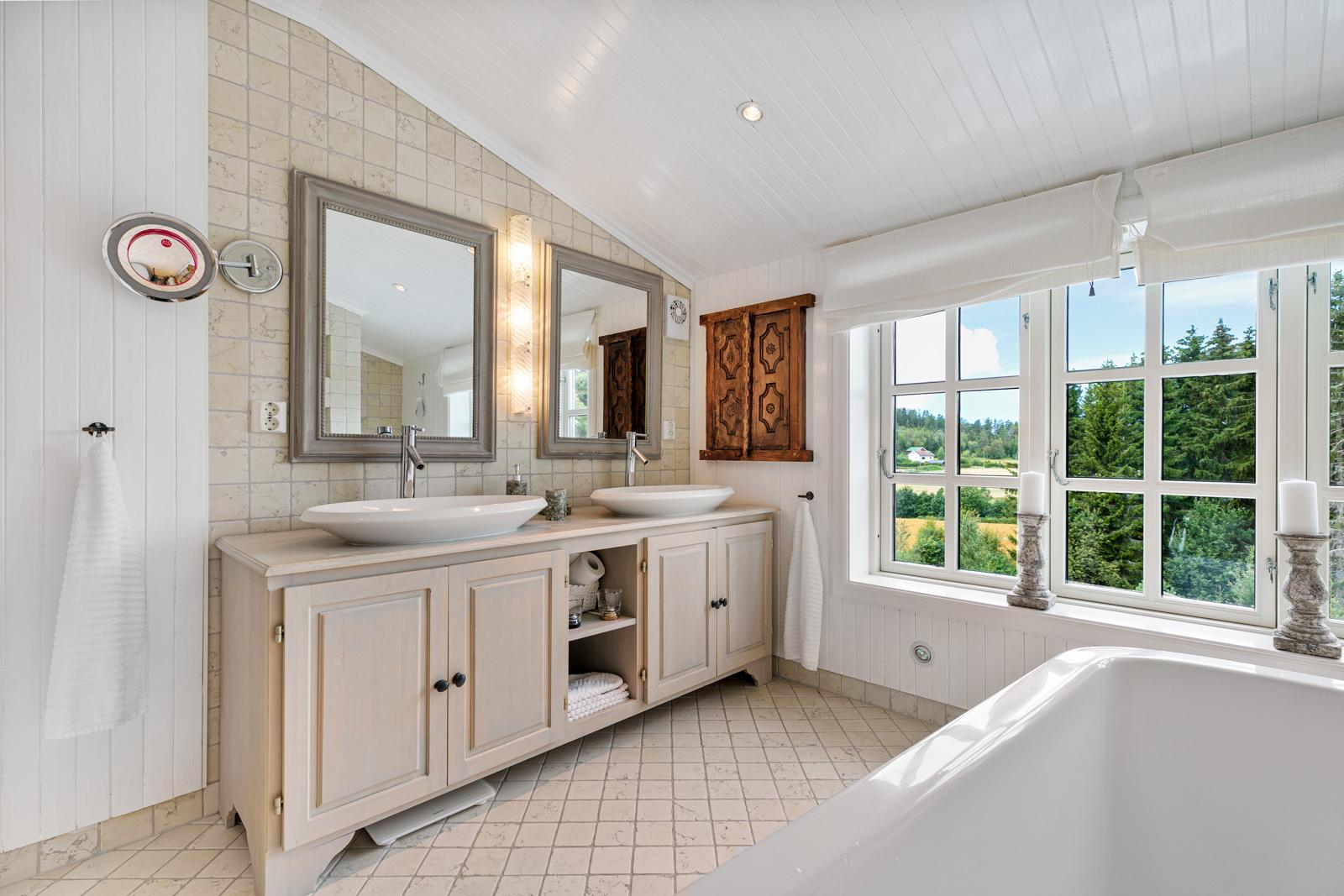 Badet i 2. etasje er stort med badekar, dusj, dobbel servant og toalett