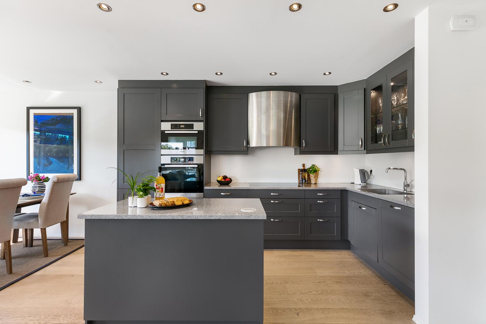 Lekkert kjøkken med downlights og integrerte hvitevarer.