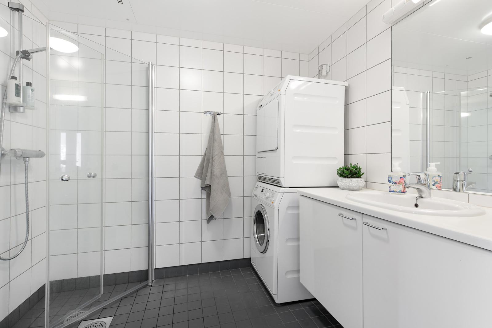 Flislagt bad/wc med varme i gulv, dusjvegger og plass for vaskemaskin.