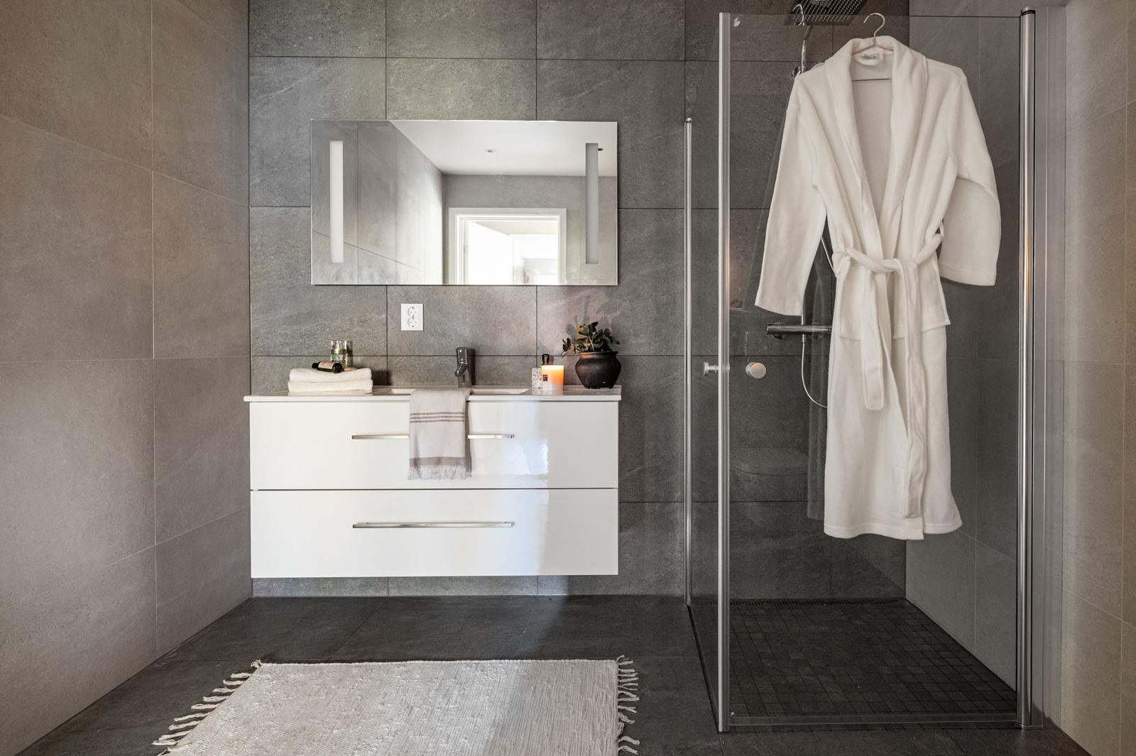 Bad. Det er svingbart dusjhjørne og vegghengt toalett.